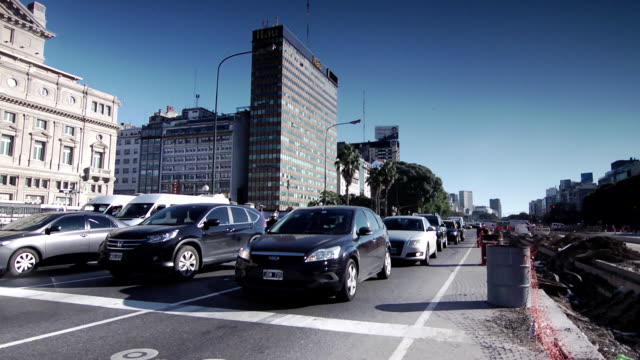 angled city street, skyscraper, mid-rise buildings, rapid motion: vehicles, cars, taxis, motorcycles, driving down road. - plaza de la república buenos aires stock videos & royalty-free footage