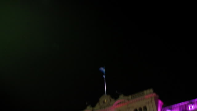 Angled WS TD Dark sky Casa Rosada w/ pink lights unidentifiable person walking