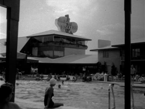 Angled WS Desert Inn pool w/ some people in water others sitting edge woman in one piece bathing suit amp swimming cap next to boy standing jumping...