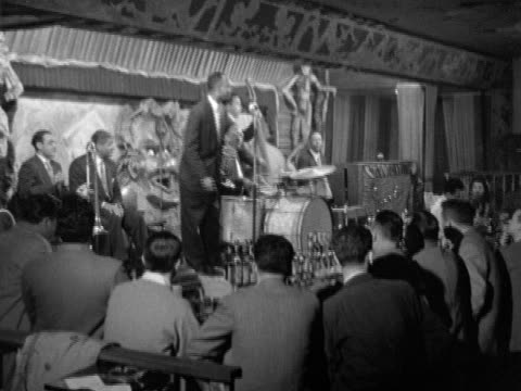 vidéos et rushes de angled dixieland jazz band musicians on elevated stage w/ men sitting at bar fg, sot playing 'when the saints come marching in', trumpet player... - la nouvelle orléans