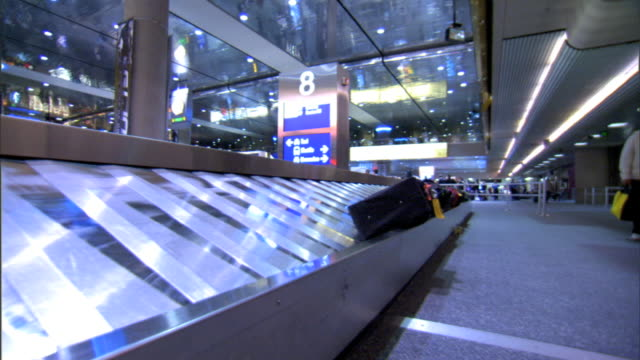 Angled WS DOLLY ALONG Baggage Claim carousel passing suitcases luggage resting along edge of conveyor unidentifiable people walking down terminal on...