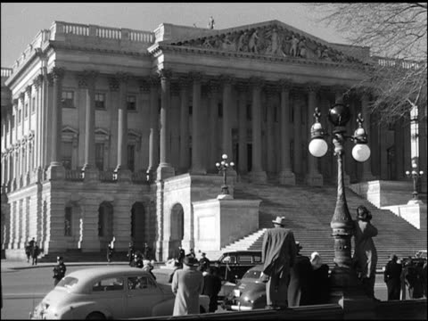 vídeos de stock e filmes b-roll de angled ws east front of capitol building w/ people standing on sidewalk watching motorcade passing front of building turning into parking area ws... - 1947