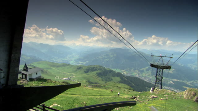 angled mountain side w/ small building, cables & cable tower w/ valley below reveals large valley. - 北チロル点の映像素材/bロール