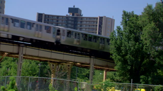 vidéos et rushes de hd angled ms elevated train moving across tracks above chainlink fence trees highrise building bg city urban metro heavyrail rapid transit - rapid city