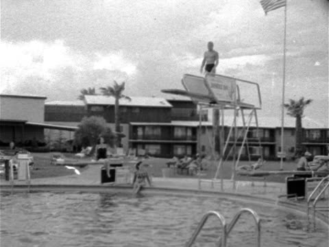 Angled WS End of pool w/ male on highdive board diving into pool two females in onepiece bathing suits watching people on beach chairs amp hotel BG...