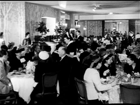 Angled WS Fairmont Hotel w/ traffic FG UPSCALE DINING Dining room Women in hats dining w/ men in suits Dessert tray in front of bottles of champagne...