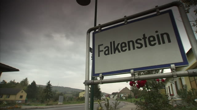 angled ws falkenstein sign inside metal pipe frame on side of town road houses along curved street bg heavy cloud cover in sky above state of lower... - lower austria stock videos and b-roll footage