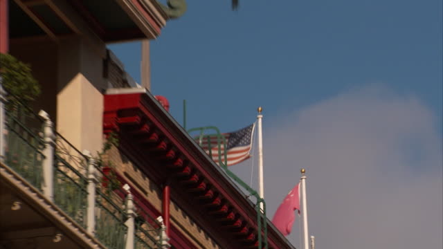 angled cu flagpoles w/ united states china flags on roof zo ms revealing midrise buildings w/ balconies signs w/ chinese characters red paper... - hanging sign stock videos and b-roll footage