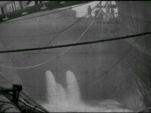 vídeos de stock, filmes e b-roll de angled ws foggy dock w/ men walking ship ramp ws side of us navy ship dumping ballast water - 1943