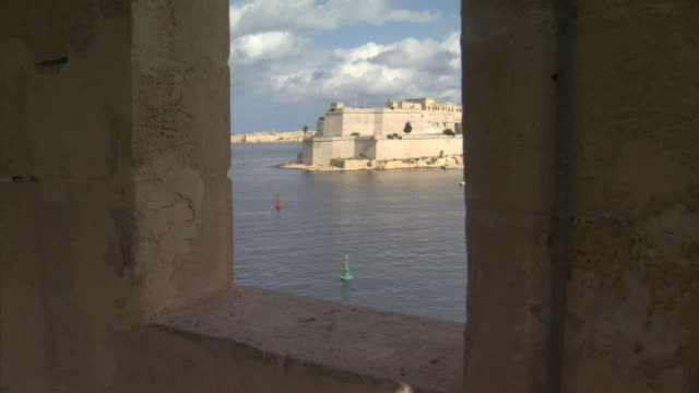 ha angled ls open window framing fort san angelo across valletta grand harbour in birgu w/ channel markers in mediterranean sea below fg peninsula... - valletta stock videos & royalty-free footage