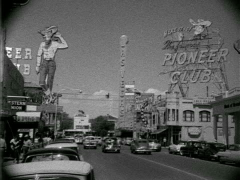 vídeos y material grabado en eventos de stock de angled ws fremont street w/ cars parked curbside fg casinos amp traffic large 'vegas vic' sign above building pioneer club sign w/ 'vegas vic' head... - 1952