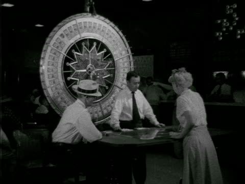 vídeos de stock e filmes b-roll de angled gamblers, male sitting, woman standing at table in front of large wheel w/ labels of bills, male dealer turning wheel, players placing chips,... - 1952