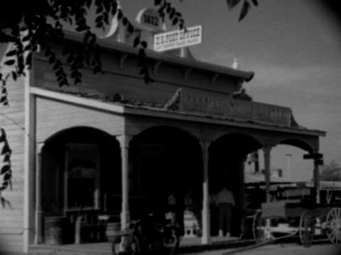 stockvideo's en b-roll-footage met shopping angled ws general store amp post office ws two women looking at carved wooden 'indian' in front of leather shop tourist trade shops... - 1952