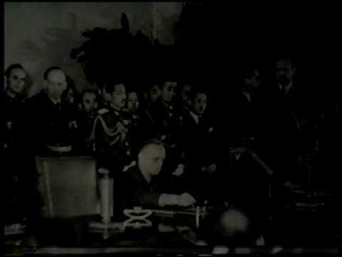 angled ws german foreign minister joachim von ribbentrop sitting at table w/ others bg ots ribbentrop signing name japanese ambassador saburo kurusu... - 合意点の映像素材/bロール