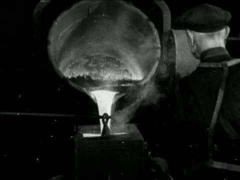 Angled WS Gilette Johnston bell foundry VS Molten metal in large hanging bucket being poured into mold MS 'RecastCoronation of Queen Elizabeth II AD...