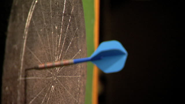 angled cu gray dartboard hanging on wall w/ soft bg dart w/ blue flight sticking in section fg two into sections behind first next to each other male... - dart stock videos & royalty-free footage