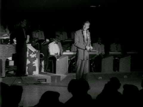 angled ws humorist herb shriner on stage sot joking about his wallet live band sitting bg audience in silhouette fg possibly hotel last frontier - 1952 stock videos and b-roll footage