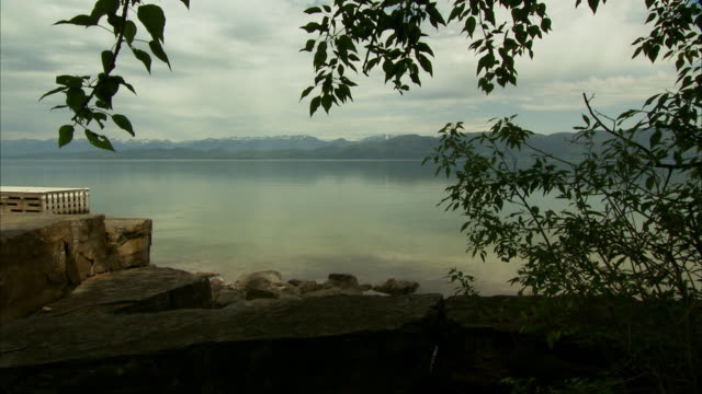 angled lake w/ mountains bg, cut boulder stone divider lining lakefront property, rocks along shore, low clouds but sunny near shore, framed by... - boulder rock点の映像素材/bロール