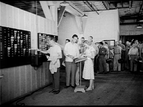 vídeos de stock e filmes b-roll de angled ws long building vs people standing in line at work taking new time card from woman w/ cards in box 'punching in' on time clock precomputer... - 1947