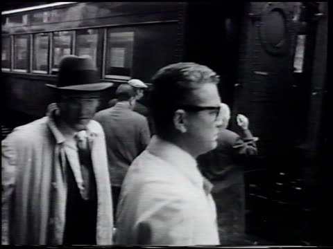angled ws long island railroad train pulling into station rob cox getting onto train w/ other commuters ms rob reading newspaper 1949 photo rob 'true... - long island railroad stock videos and b-roll footage