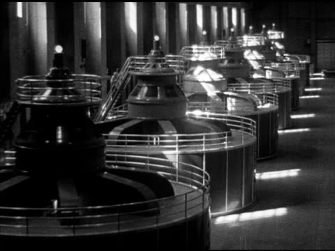 angled ws long row of power plant turbine generators w/ male worker climbing to top of stairs working upper level ha td ws top of dam w/ cars parked... - elektrischer generator stock-videos und b-roll-filmmaterial