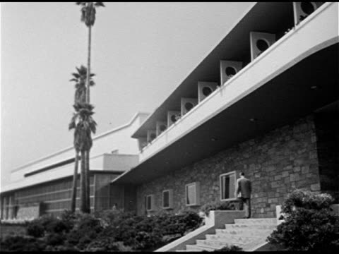 Angled WS Male walking up steps of midcentury modern office building Man walking by men's store display window HOLLYWOOD WS Brown Derby restaurant on...