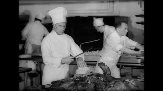 stockvideo's en b-roll-footage met hd angled ms man in chef's hat cutting slices of meat from cooked turkey breast at end of commercial kitchen table w/ baked turkeys fg man in suit... - 1949
