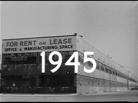 Angled WS Manufacturing warehouse factory w/ 'For Rent or Lease' sign '1945' Superimposed over building POST WWII INDUSTRY Exterior of two Large...
