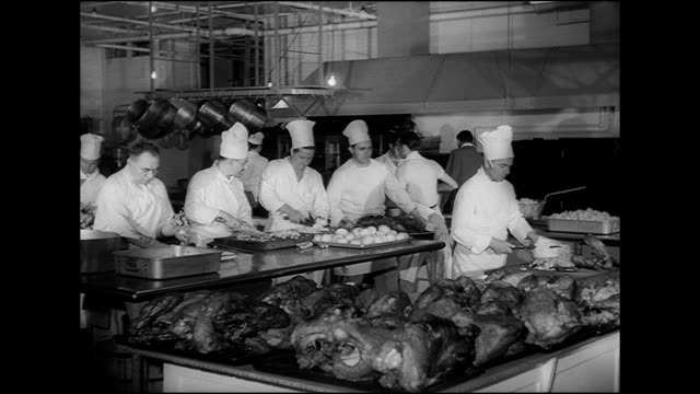 vidéos et rushes de hd angled ws men working in large commercial kitchen some in chef's hats chopping food on prep table male carving turkey at end of table lined w/... - 1949