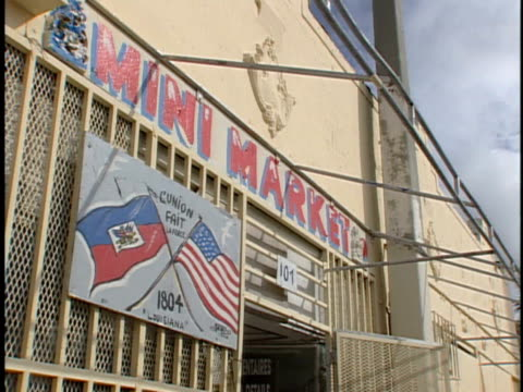 *angled ms mini market in older building w/ hand painted haiti american flag sign w/ l'union fait la force between dated 1804 at bottom attached to... - haiti stock-videos und b-roll-filmmaterial