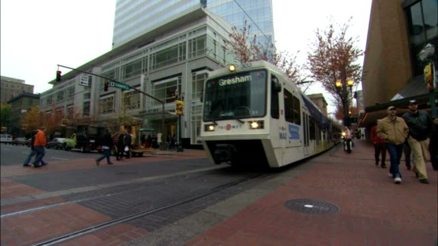 Angled WS Modern light rail streetcar moving through frame people crossing street city stores BG