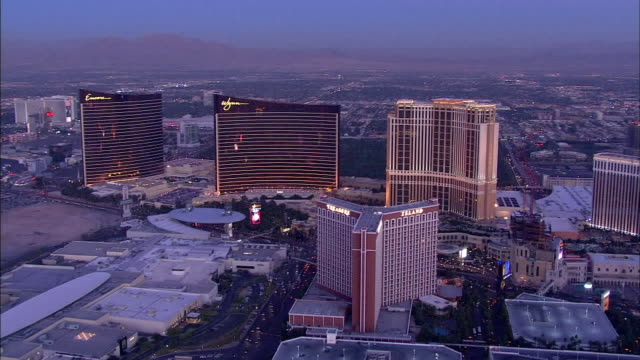 angled treasure island, palazzo across the strip next to wynn las vegas twin towers, tuning east to include venetian hotel & casino. - the palazzo las vegas stock videos & royalty-free footage