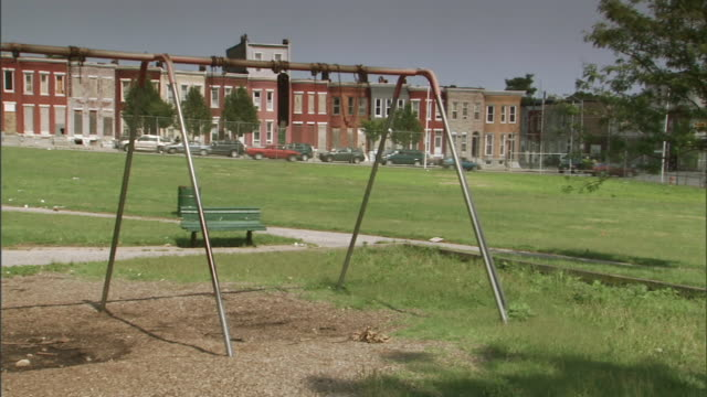 vídeos y material grabado en eventos de stock de hd angled ws open grass park w/ broken swings wrapped around swing set frame top row houses cars parked curbside bg some traffic - baltimore maryland
