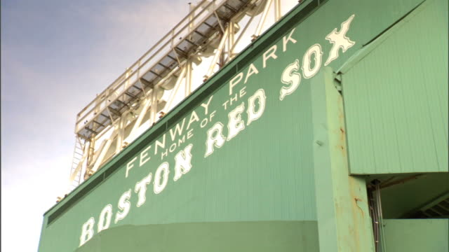 TU Angled WS Painted sign on exterior green wall of baseball park Fenway Park Home of the Boston Red Sox back of elevated sign catwalk above