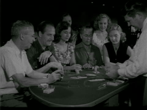 angled ws people sitting at blackjack table w/ dealer standing woman turning in playing cards in dealer dealing card to 'house' paying out to winning... - dealing cards stock videos and b-roll footage