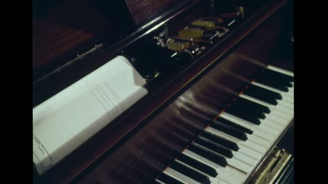 vídeos y material grabado en eventos de stock de angled player piano playing, keys moving up, down & paper music roll rolling forward on spool, holes on music roll paper moving down through frame to... - bobina