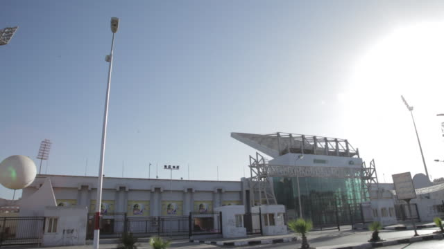 Angled WS Port Said Stadium w/ cars motorcycle driving through FG
