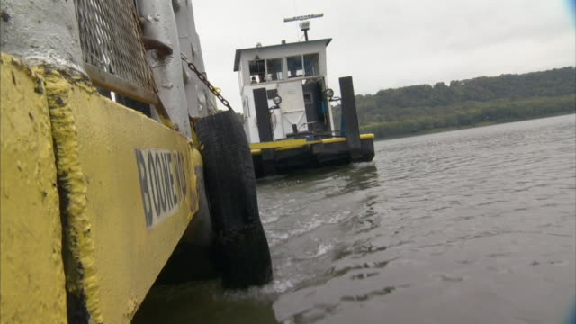 vídeos y material grabado en eventos de stock de angled ws push boat working near stern moving barge across river boone 7 lettering on yellow side w/ tire bumper chained to ferry fg opposite shore... - río ohio