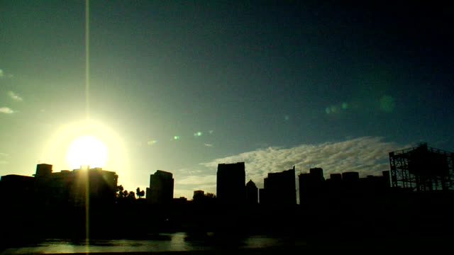 angled pre-dawn to day time lapse, sun rising up from behind downtown business district high-rises, skyscrapers in silhouette, rapid motion clouds... - moving up点の映像素材/bロール