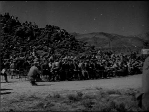 angled ws press people sitting in chairs on hill wearing protective goggles everyone cringing at once xws smoke rising in streams cloud above distant... - 1952 stock videos and b-roll footage