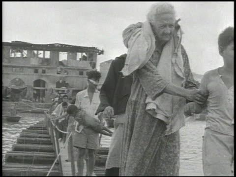 angled ms refugees displace persons walking across pontoon bridge filipino boy leading elderly woman injured man carrying half dressed baby woman... - pontoon bridge stock videos and b-roll footage
