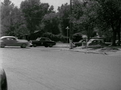 angled ws residential neighborhood intersection police patrol car turning corner driving fast down out of frame tracking car passing policeman patrol... - 1952 stock videos and b-roll footage