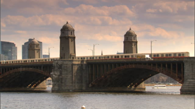 angled ws reverse pan longfellow bridge w/ traffic train passing towers ws city w/ charles river fg - チャールズ川点の映像素材/bロール