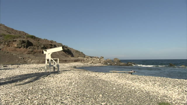 angled rocky cove beach w/ empty lifeguard chair, rock jetty, caribbean sea to rocky cliff w/ partial cable beach rules freestanding sign fg. - lifeguard chair stock videos & royalty-free footage