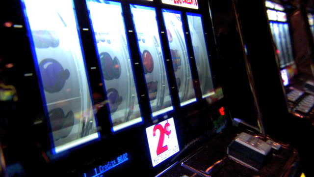 angled ls row of slot machines one near end in use middleaged female hand w/ middle finger daintily pushing button electronic gaming gambling luck... - fruit machine stock videos & royalty-free footage