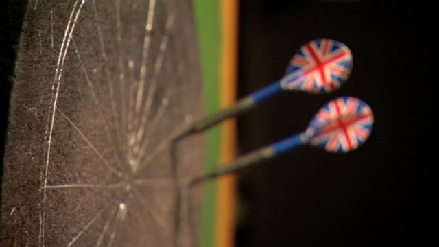 angled cu gray dartboard hanging on wall soft dart w/ union jack flight stuck in section bg second sticking just above third dart sticking section fg... - dart board stock videos & royalty-free footage