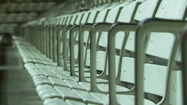 angled vintage older wooden slat & metal seats w/ tall arms in row, soft to out of focus seating to row end. no people. - amphitheatre stock videos & royalty-free footage