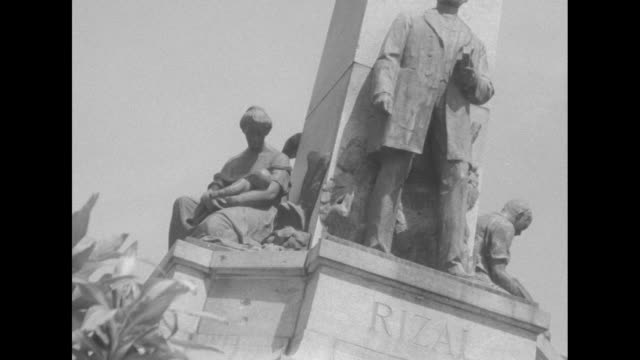 cu angled shot of man in doorway drinking from cup / ms street crowded with pedestrians and some trucks / cu angled cu jose rizal monument / ships in... - push cart stock videos and b-roll footage