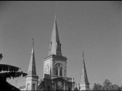 angled ws spires of saint louis cathedral td ws cathedral w/ tree tops fg people's heads moving across lower frame roman catholic church religion - catholicism stock videos & royalty-free footage