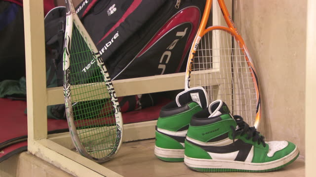 angled ws squash gear pair of shoes two racquets leaning on wooden frame sports bags bg [sot squeaking shoes on court squash ball hits] - squash sport stock videos & royalty-free footage